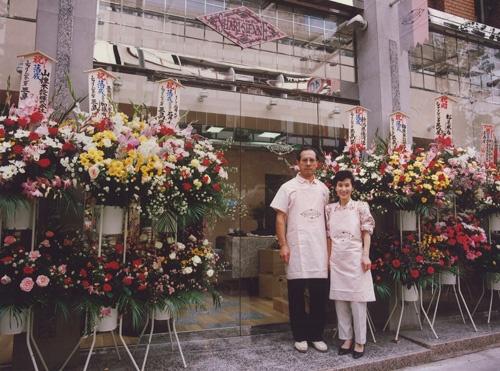 新保圭司郎さんと妻のまさみさん。1989年、改装したばかりの三島屋の前で(東京都新宿区)