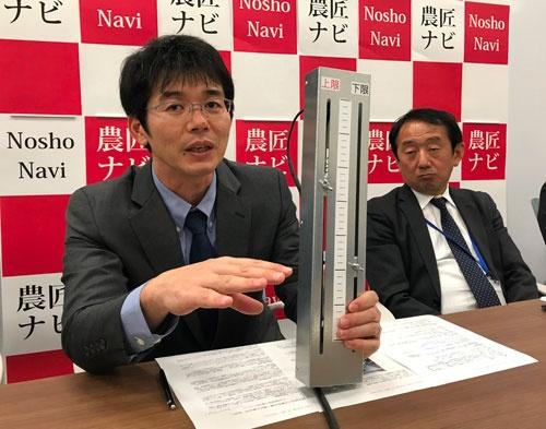 「自動給水機は農家の目線で作った」と話す横田修一氏。手にしているのはセンサーの部分(都内で開かれた説明会)