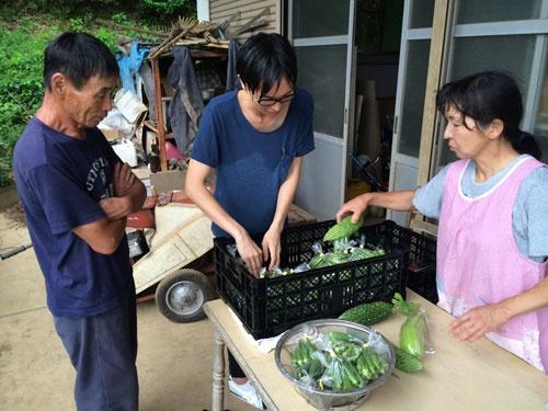 山川さんはベテラン農家の柚木実さん㊧と徐々に打ち解けた。右は妻の充子さん(多摩市)