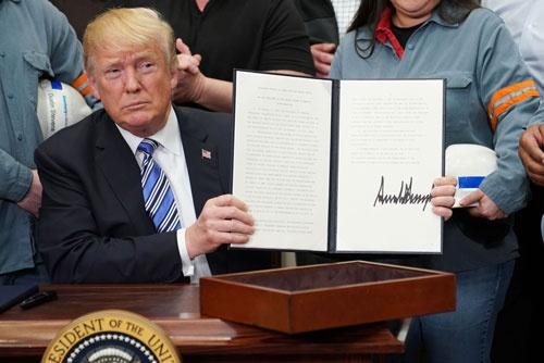 3月8日に大統領令に署名したトランプ大統領(写真:AFP/アフロ)