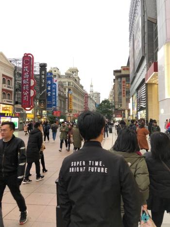 「素晴らしい時間、明るい未来」という若者が背中に背負って歩けるという中国の現実(上海南京東路。2018年12月)