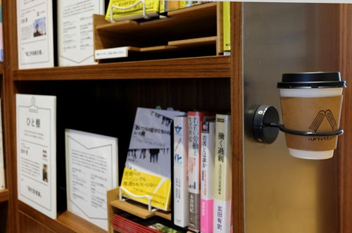 本棚に設置されている飲み物用ホルダー。気になる本があったら飲み物を預け、フリーハンドになれる