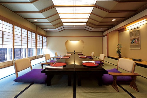 赤坂浅田のお座敷。雪見障子から差し込む光と照明が作り出す、料亭ならではの凛とした空間。正面に見える床脇の「刳形(こがた)」の棚が印象的