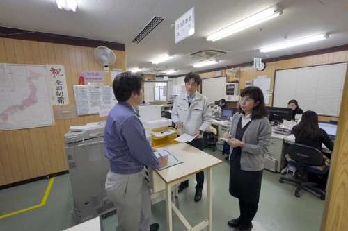 群協製作所ではL字型オフィスの角に社長席と打ち合わせ席がある。どちらも立ち席で周囲がよく見え、遠山社長(左)は社員の働きぶりに気を配る(写真:新関雅士)