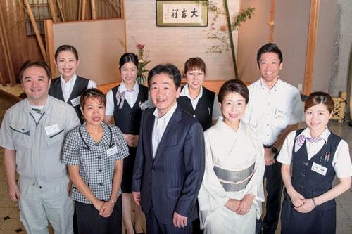 山口専務(前列中央)と女将(その右)を囲んで社員が集合。休みが増えて、気持ちに余裕が生まれたことで、今まで以上に明るい笑顔でお客をもてなせるようになった(写真:山岸政仁)