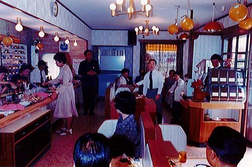 1974年に妻の直美氏(立っている女性)と喫茶店「バッカス」を開業。右下の後ろ姿の男性が宗次氏