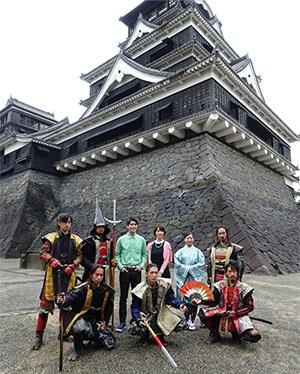 映画『Hand in the Glove』のロケ地の熊本城で、撮影の合間に記念写真を撮る出演者と観光PRを担う「おもてなし武将隊」。中央のグリーンのシャツが主演のチャーノン・リクンスラガーン氏
