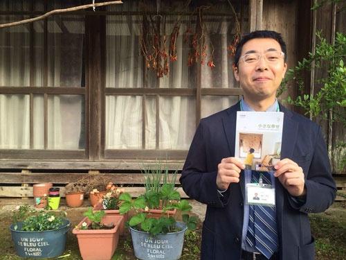 タイでは日系企業で輸出入業務に携わっていた鈴木良太さん。手にしているのは友人ノンさんが著したベストセラー「小さな幸せ」だ。