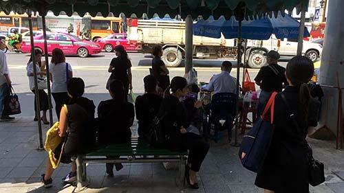 バス停でバスを待つタイ人たち。ほぼ全員が黒い服を着ている。黒で染まったバス停は初めて見た。