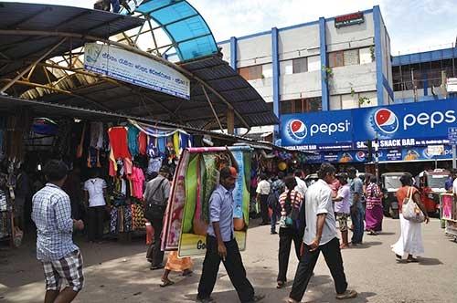 経済の中心地、コロンボ港近くのマーケット。外資企業の看板が目に入る