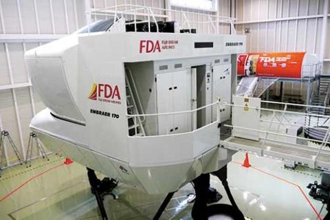 <b>国内唯一となるエンブラエル機のフライトシミュレーター。奥に見えるのは、脱出訓練などを行うモックアップ。この設備のために約20億円を投資をした</b>