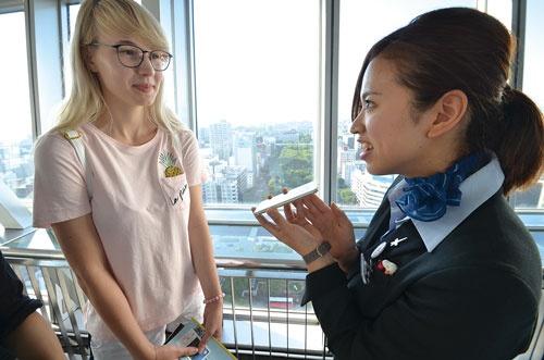 <b>名古屋テレビ塔では情報通信研究機構が開発した多言語翻訳アプリ「ボイストラ」が活躍。アテンダントの武藤さん(右)はスウェーデンから来たイリジンさんに付近の観光スポットを説明した</b>(写真=坂田 亮太郎)