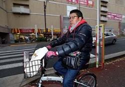 自ら自転車でチラシを配る星﨑氏。1時間程度かけて回る(写真=竹井 俊晴)
