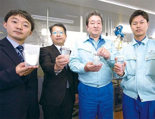 紙の原料であるパルプから作る新素材「CNF(セルロースナノファイバー)」を手にする日本製紙の研究員ら(写真=稲垣 純也)