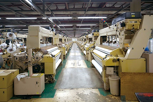 <b>何十台もの織機が整然と並ぶ第一織物の本社工場</b>