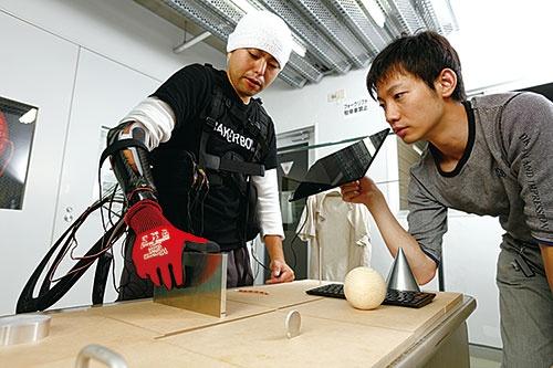 「サイバスロン」では様々なモノをつかみ移動させる競技も。右はソフト開発などを手掛ける粕谷氏(写真=竹井 俊晴)