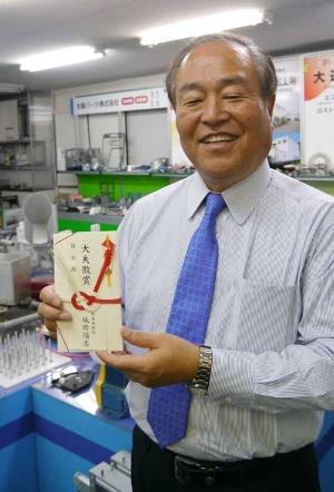 自分が選ばれた「大失敗賞」の目録を持つ城岡陽志社長