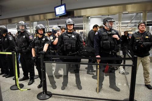 2017年1月28日、大統領令による入国制限を受け、米国サンフランシスコ国際空港第4ターミナルのセキュリティチェックポイントをブロックする警官ら(写真:ロイター/アフロ)
