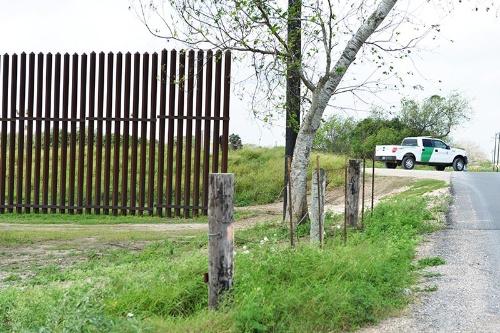 道路のところで切れた国境のフェンス。奥に見えるのは巡回しているボーダーパトロールの車両