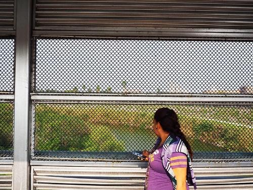 国境の橋を渡る人々。金網の向こうに見える小さな川が両国を隔てるリオグランデ川 (写真:Miguel Angel Roberts、以下同)