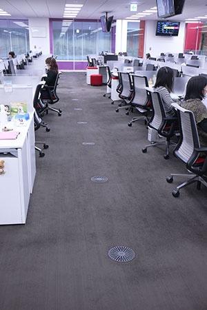コールセンターの様子。床に等間隔で埋め込まれているのが、特注で作った空調(写真 都築 雅人)