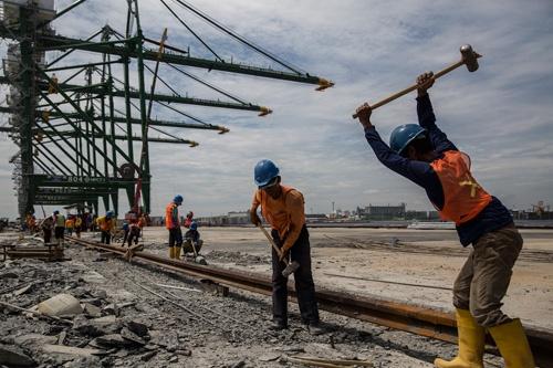 新しい国際コンテナターミナルでレール敷設を進める作業員
