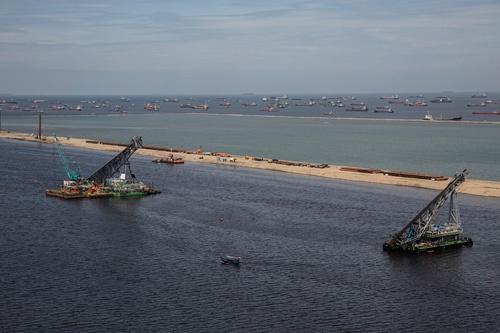既存の国際コンテナターミナルはフル稼働で、積み下ろしを待つタンカーが港で渋滞してしまう(写真上部)
