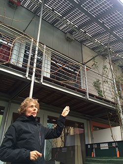 自宅の屋根に設置した太陽光パネルを示しながら資産価値について説明するマイヤーさん