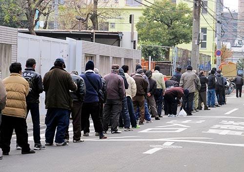 大阪市西成区のあいりん地区(釜ヶ崎)で、無料の夕食の配給に並ぶ労働者の人たち。(写真:AP/アフロ)