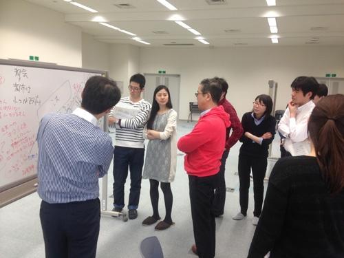 次官プロジェクトに参加する菅原事務次官。赤いパーカー姿で若手官僚らとざっくばらんに意見を交わす(左から4人目)