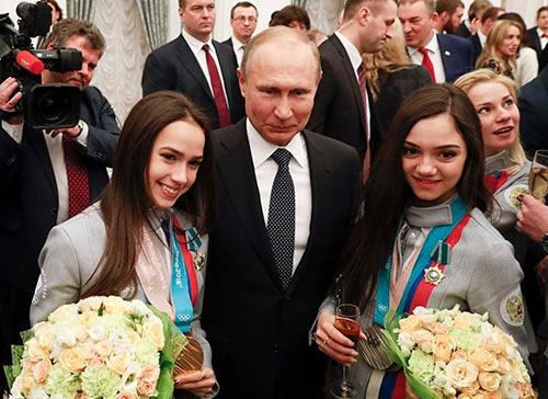 平昌オリンピックのメダリストに勲章を授与するプーチン大統領(中央)。左は金メダルを獲得したアリーナ・ザギトワ選手、右は銀メダリストのエフゲニア・メドベージェワ選手(写真:ロイター/アフロ)