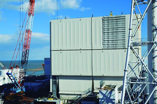写真1■ 1号機原子炉建屋の西面。1号機ではクリーム色をしたカバーの解体が始まった。作業は750t吊りクローラークレーン(左手)を遠隔操作して清水建設が進めている。屋根は2015年10月5日に撤去済みだ(写真:代表撮影)