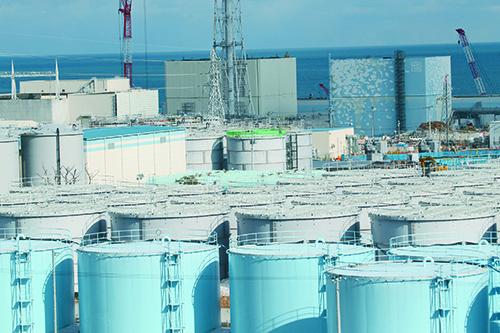 発電所に広がるタンクエリア。ボルトで組み立てるフランジ型のタンクで大量の汚染水漏れが発生したため、東京電力は溶接型タンク(写真手前)に置き換えている。2015年1月には、タンクを施工した安藤ハザマの社員が検査中に転落して死亡する事故が発生した(写真:代表撮影)