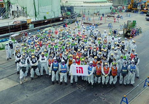 凍土遮水壁の工事を担当する鹿島の社員や協力会社の作業員。放射線量が高い原子炉建屋の周囲で作業しなければならないため、全面マスクやタングステンベストを着用している(写真:鹿島)