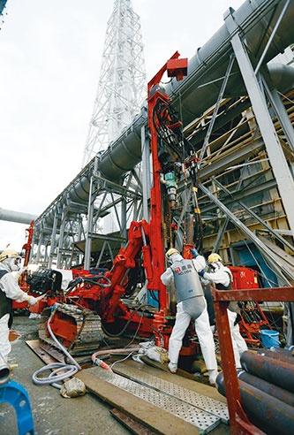 写真1■ 凍結管の建て込みに向けて、ロータリーパーカッション式のボーリングマシンで削孔する様子。ケーシングは1.5mずつ継ぎ足す。2014年7月9日に撮影 (写真:代表撮影/ロイター/アフロ)