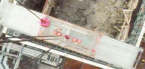 写真3■ クレーンに搭載したカメラで、吊り上げた屋根パネルの上部を見たところ。写真上に見えるのが1号機原子炉建屋(写真:東京電力)