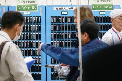 APD(警報付き個人線量計)の貸し出し装置と作業員(写真:日本記者クラブ取材団代表撮影)
