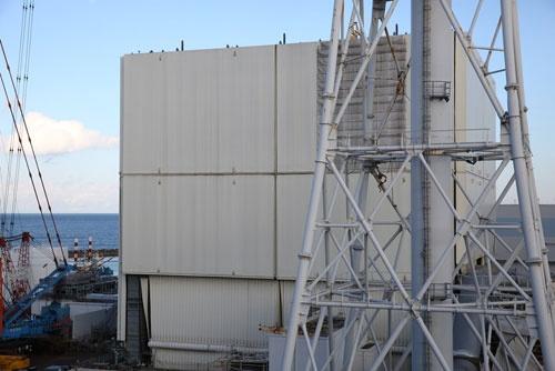 1号機原子炉建屋では、がれきの撤去に手を付けるために、クリーム色をしたカバーの解体が始まった。既にカバーの屋根は撤去済みだ(写真:日本記者クラブ取材団代表撮影)