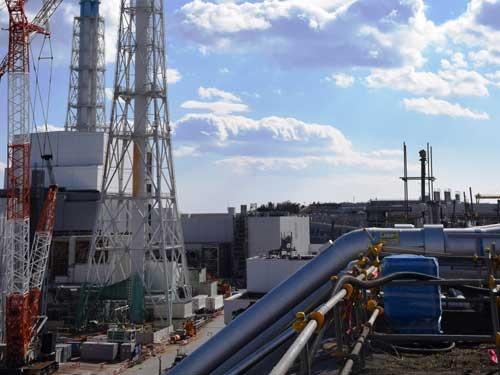 OP35m盤の高台に設けたプラントから、OP10m盤にブライン(冷却液)を供給する配管。左手に見えるのは4号機原子炉建屋とカバー(写真:日本記者クラブ取材団代表撮影)