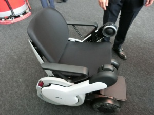 WHILLの「WHILL NEXT」は、人が座って乗る車椅子型のパーソナルモビリティー。遠隔操作で降りた場所から自動回収もできるという。