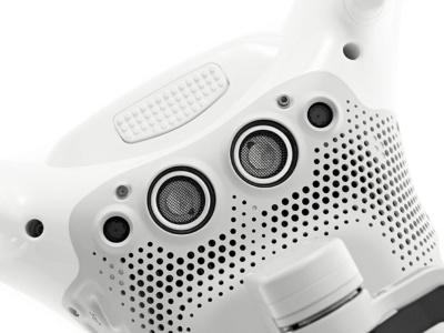 Phantom 3では、ビジョンポジショニングシステムの音響センサー(写真中央の大きな2つの丸部分)2個とカメラが1つだったが、Phantom 4ではカメラを2つ(両脇の黒い丸部分)にすることでその精度を約5倍に向上させた