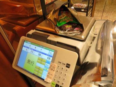 菓子を入れた袋を計りに乗せて計量する。1グラム3円で、1袋だいたい500円前後