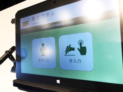 チェックイン時はフロントに近づくと恐竜ロボットが「タッチパネルで言語を選択してください」とアナウンス。使用言語を選択後、「音声入力」と「手入力」を選択。音声入力を選択すると「僕に向かってお名前をお話しください」とアナウンスがあり、名前を言うとタッチパネルに登録済みのデータが表示される。確認後、サインをすると隣の精算機から領収書とカードキーが発行される
