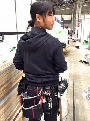 工具袋を腰に下げた設営女子。七つ道具はカッター、ペンチ、メジャー、電動ドリルなど(画像提供:基陽)