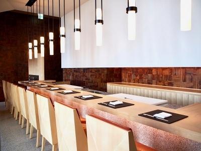 中之島はかつて蔵屋敷が立ち並ぶ町だったことから「蔵」と名付けられた寿司&鉄板焼きのコーナー。ヒノキのすしカウンターは全9席。1万枚もの漆のピースを手張りで何層にも重ねた壁が、店内を緩やかに仕切り、折り紙から着想を得た和モダンな空間を演出