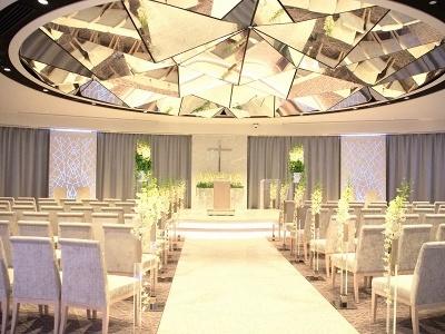 広さ150平米のウェディングチャペル。日中は日差しが降り注ぎ、夜にはジュエリーボックスのようなロマンティックな空間が広がる。白い大理石のモザイクで作られたバージンロードとダイヤモンドのような天井の照明も印象的