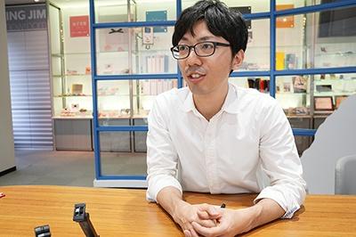 キングジム開発本部商品開発部開発二課の木次谷氏。ガラス天板を採用することで人気が出た机上台「デスクボード」の開発も担当