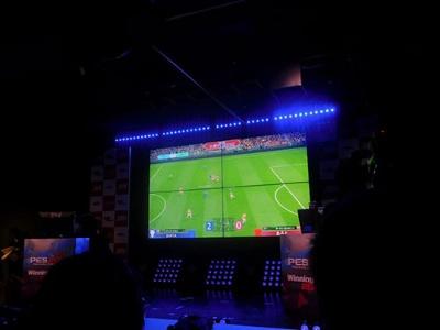 試合中の会場の様子。スクリーンには、あると選手とSOFIA選手の試合風景が映し出されている。なお、決勝に進出した4選手ともに使用チームはアーセナル(イングランド)だった