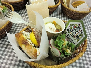 新商品の「たっぷり国産キャベツのメンチ」(292円)と「いつもと違う!フライ用4種の添え野菜」(376円)を挟んだハンバーガー(写真左)、週に1500食以上売れているという「たっぷりケールのチーズナッツサラダ」(637円、写真手前)、「彩り野菜と玉子の入ったごちそうスープ」(616円、写真奥)