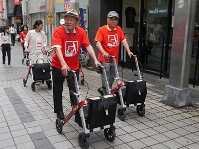 街歩きイベント「タブレット付きまちなかカートを使ってまちなかゆる歩き!!」の様子。参加者はまちなかカートを使って商店街を歩く